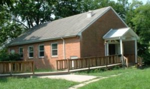 photo of meetinghouse; red brick single story building with white-roofed front porch and a long wooden ramp